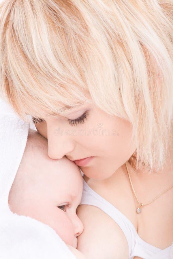behandla som ett barn amning henne kyssmodern royaltyfri fotografi