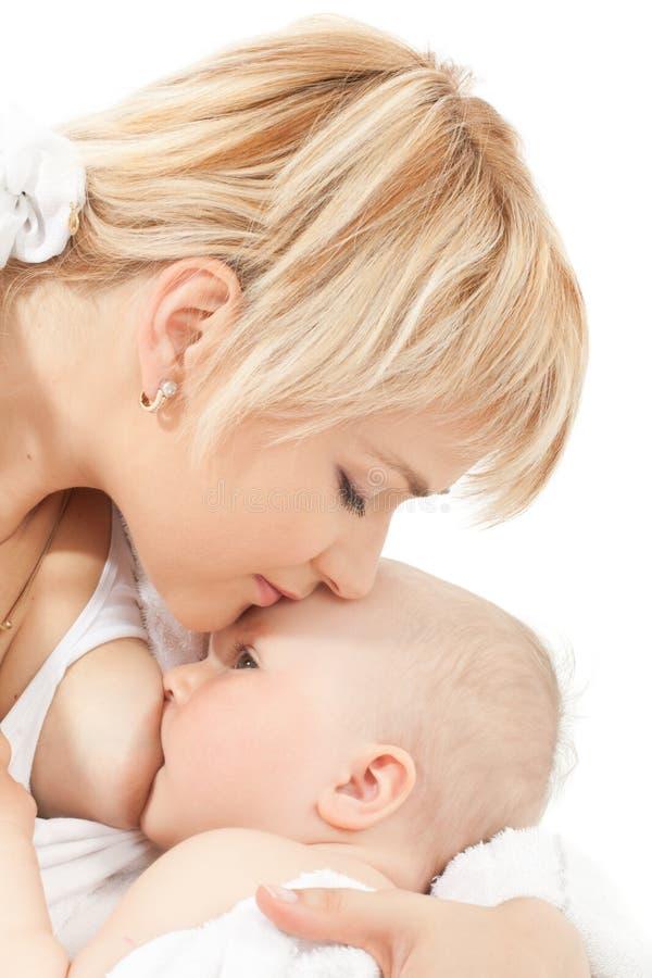 behandla som ett barn amningflickan henne kyssmodern royaltyfri fotografi