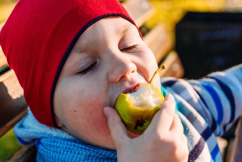 Behandla som ett barn aptitretande för att äta päronet arkivbilder
