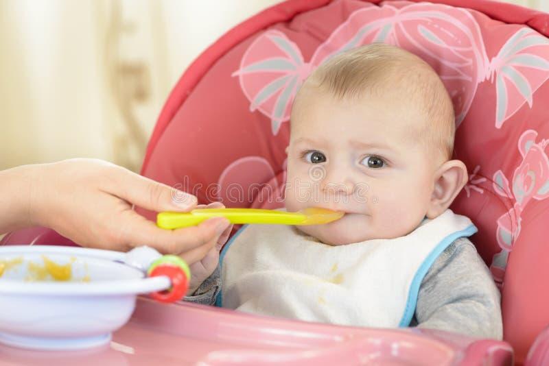 Behandla som ett barn att äta i en hög stol royaltyfria bilder
