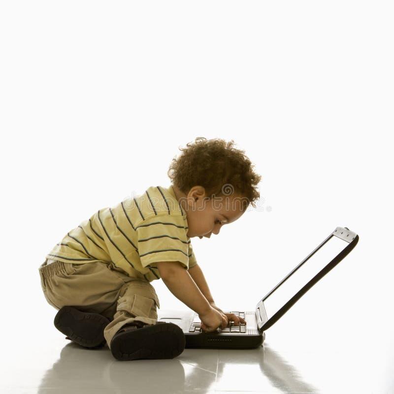 behandla som ett barn att använda för bärbar dator royaltyfri fotografi