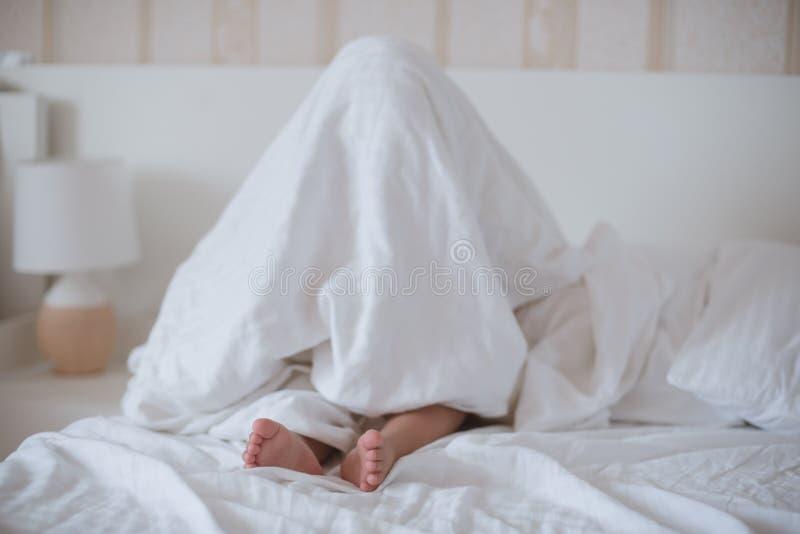 Behandla som ett barn att dölja under en vit filt som sitter på sängen arkivbild
