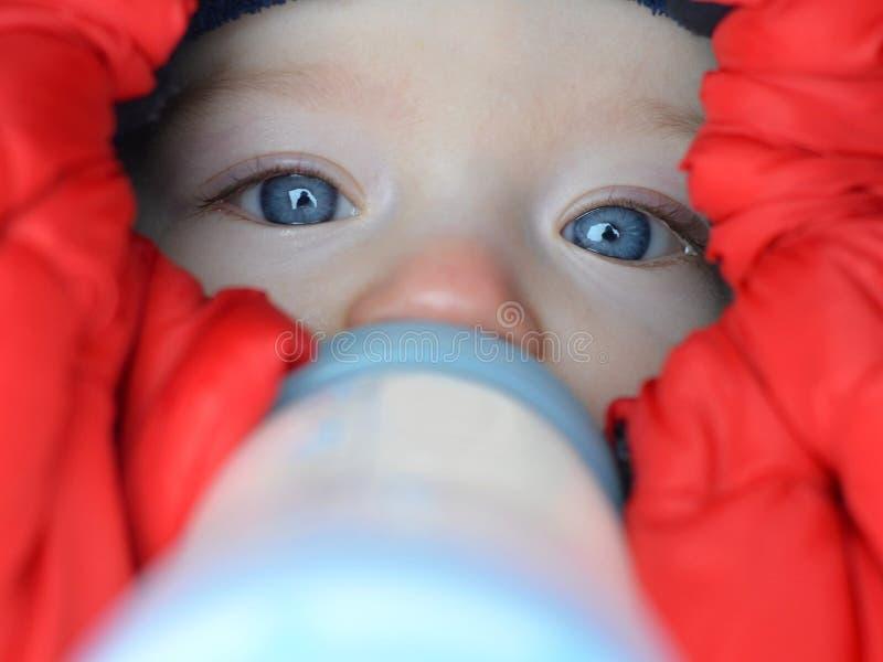 Behandla som ett barn att dricka mjölkar i footmuff i vinter royaltyfri foto