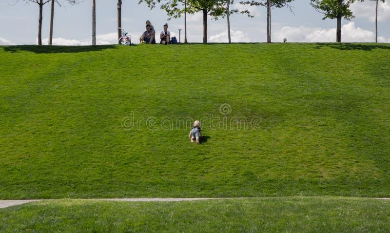 Behandla som ett barn att krypa på gräset till deras föräldrar royaltyfria foton
