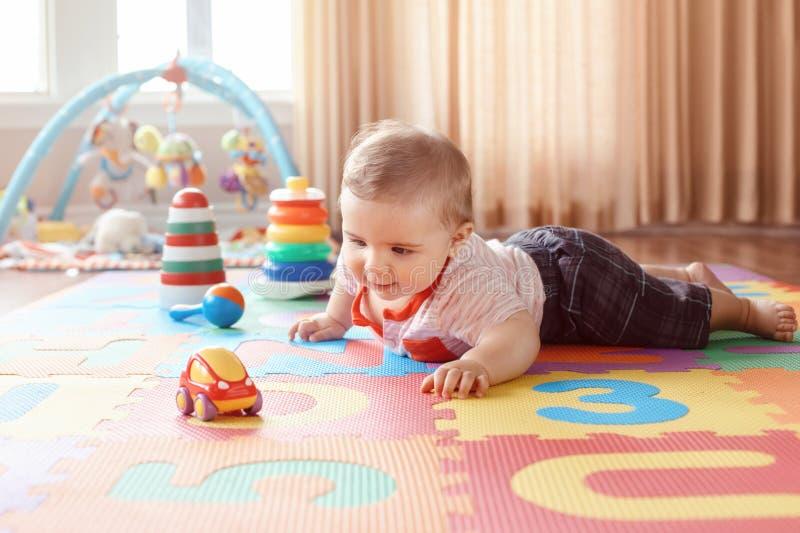 Behandla som ett barn att krypa på playmat Tidig utbildningsutveckling arkivfoto
