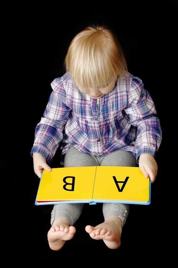 behandla som ett barn att lära för flicka som läs till arkivfoto