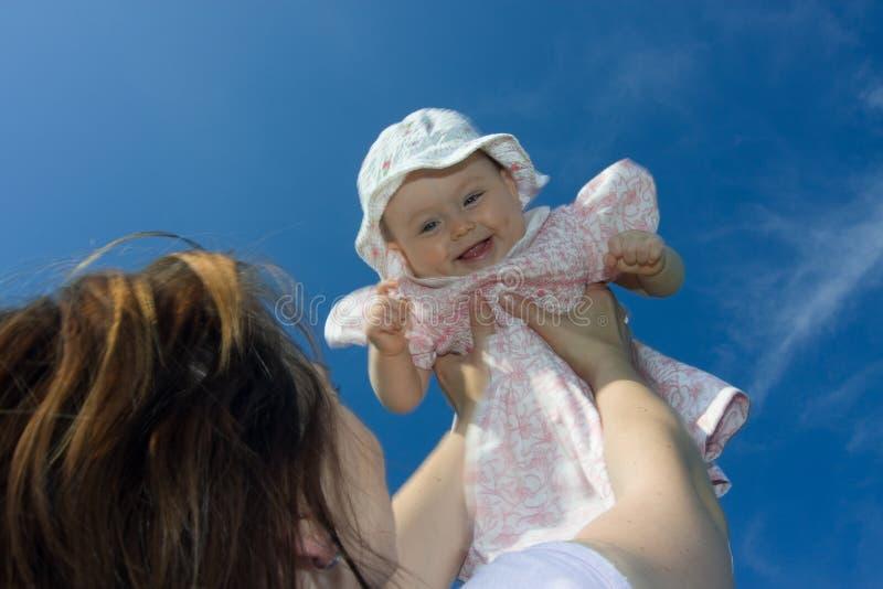 behandla som ett barn att le för holdingmoder royaltyfri foto