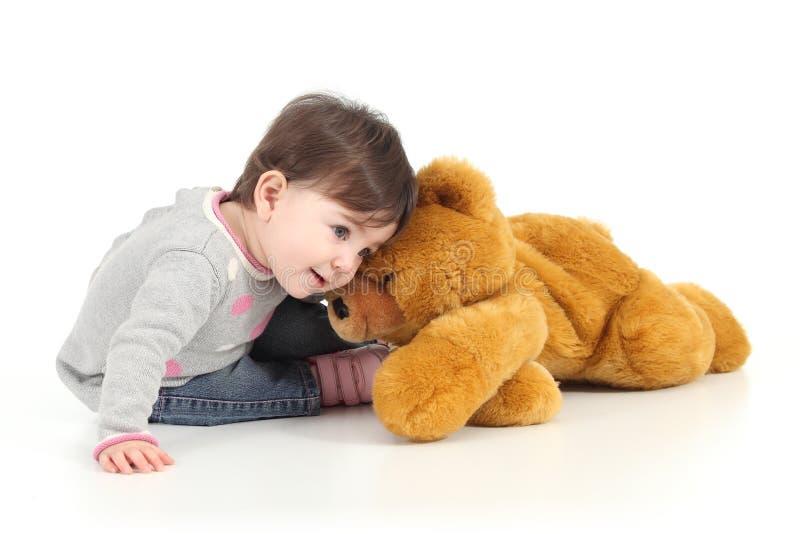Behandla som ett barn att leka med en nallebjörn arkivfoto