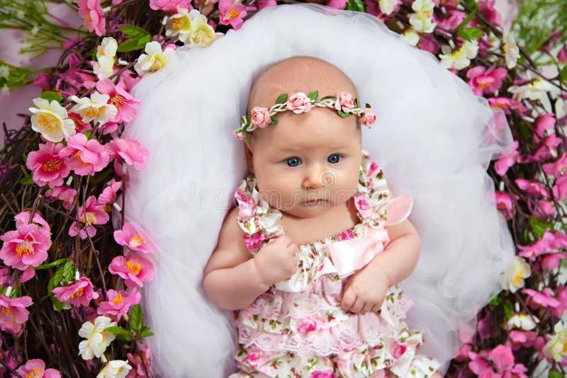 Behandla som ett barn att ligga i ett rede av blommor arkivfoton