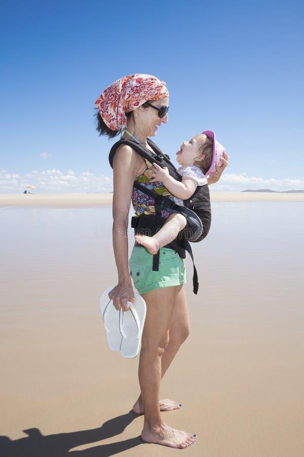 Behandla som ett barn att skratta i ryggsäck med mamman royaltyfri fotografi