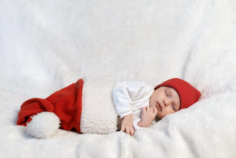 Behandla som ett barn att sova i jultomtenhattar fotografering för bildbyråer