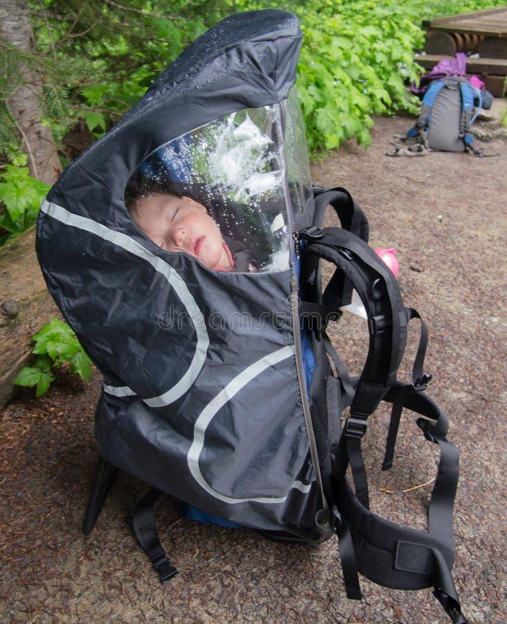 Behandla som ett barn att sova i ryggsäck arkivfoton