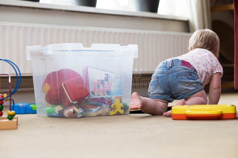 Behandla som ett barn att spela bara med leksaker p? en matta p? golvet hemma arkivbild