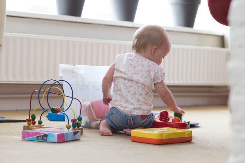 Behandla som ett barn att spela bara med leksaker p? en matta p? golvet hemma fotografering för bildbyråer