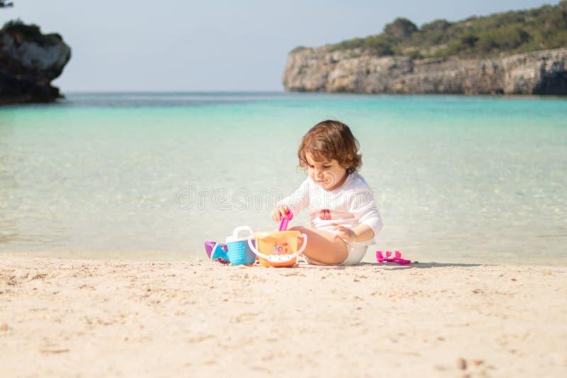 Behandla som ett barn att spela på stranden, Menorca Cala Turqueta arkivbilder