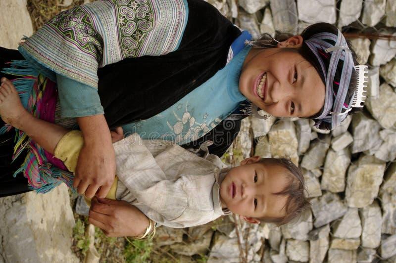 behandla som ett barn barn för hmongståendekvinnan arkivfoton