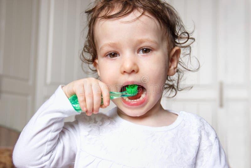 Behandla som ett barn barnborsten deras tänder riktigt med en grön tandborste royaltyfri fotografi
