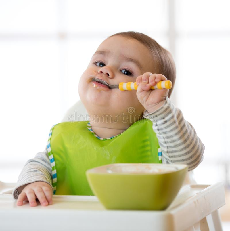 Behandla som ett barn barnet äter mat själv med skeden Stående av den lyckliga ungepojken i hög stol arkivfoto