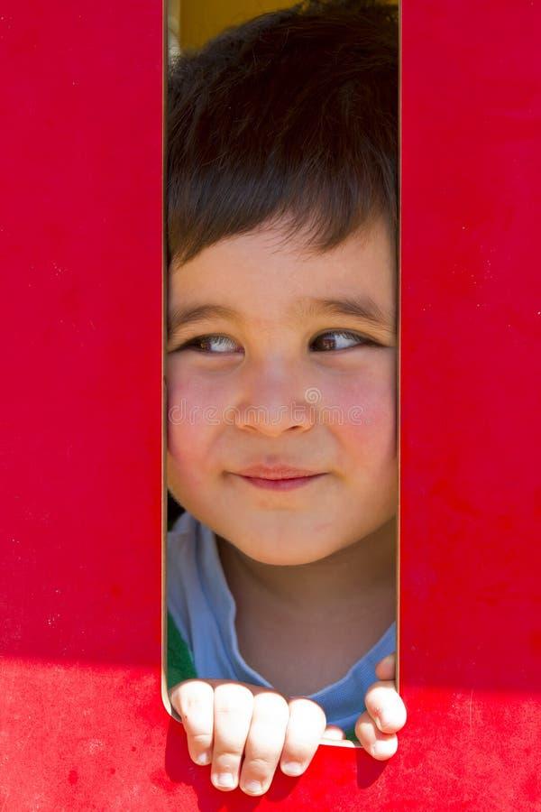behandla som ett barn barnet little park som leker röd smilling royaltyfria foton