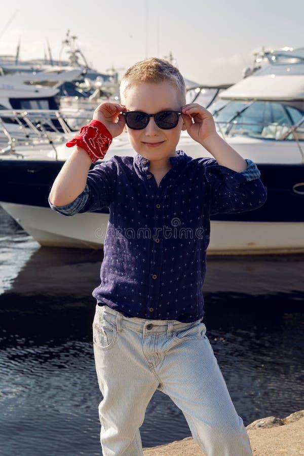 Behandla som ett barn blonda 8 år för pojken i en blå skjorta, ljus byxa royaltyfri bild