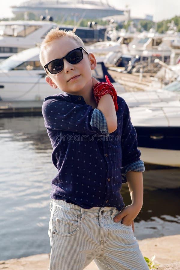 Behandla som ett barn blonda 8 år för pojken i en blå skjorta, ljus byxa royaltyfria bilder