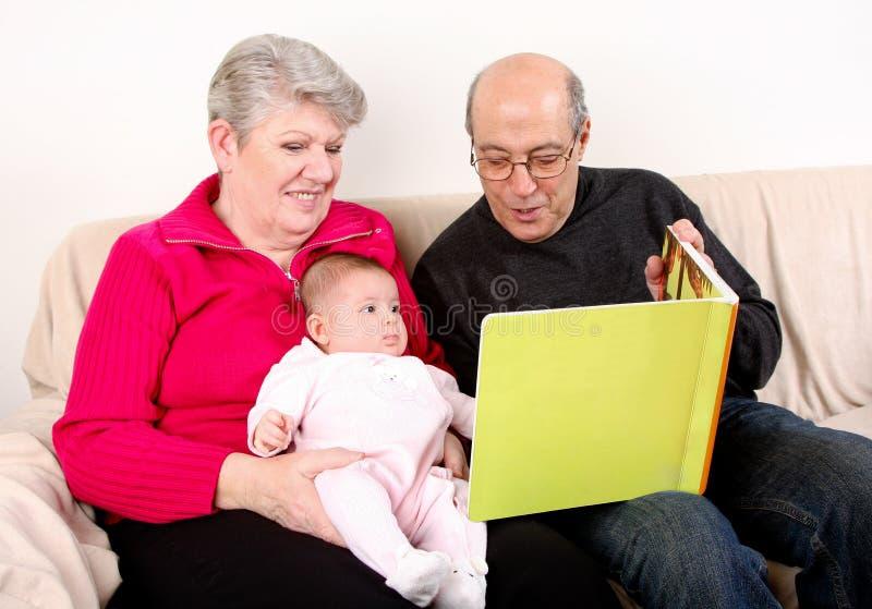 behandla som ett barn bokfamiljen som läser till royaltyfri foto