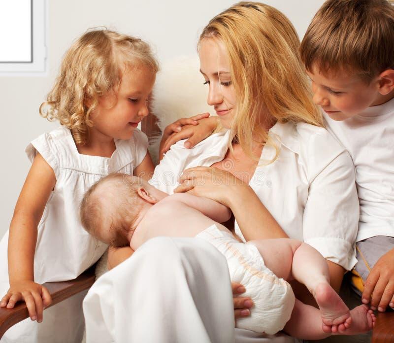 behandla som ett barn breastfeeding henne modern arkivbild
