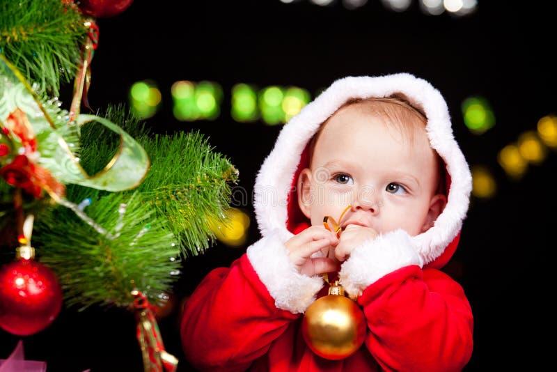 Behandla som ett barn bredvid julgran arkivfoto