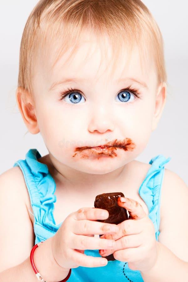 behandla som ett barn choklad äter flickan fotografering för bildbyråer