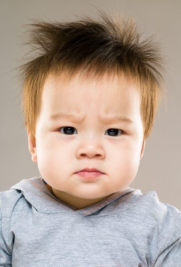 behandla som ett barn den allvarliga pojken arkivfoto
