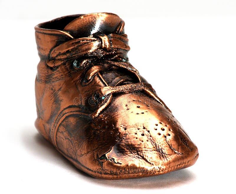 behandla som ett barn den enkla bronze skon arkivfoton