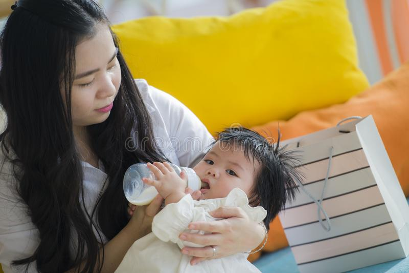 Behandla som ett barn den franka ståenden för livsstilen av den unga lyckliga och söta asiatiska japanska kvinnan som matar henne arkivfoto