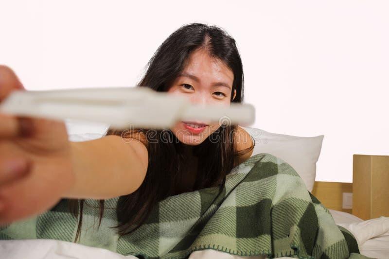 Behandla som ett barn den hållande graviditetstestet för den lyckliga och upphetsade asiatiska koreanska kvinnan som kontrollerar arkivbild