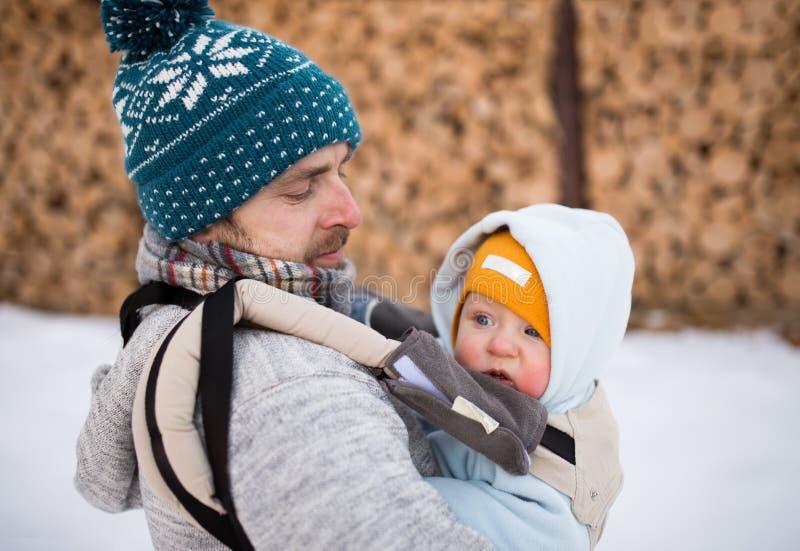 Behandla som ett barn den hållande sonen för fadern in bäraren vinter för skognatursun fotografering för bildbyråer