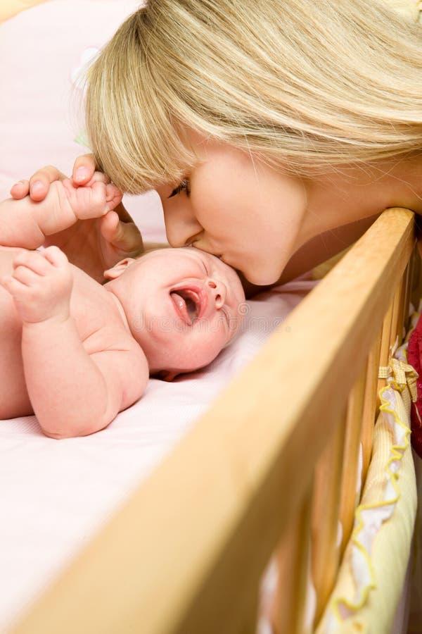 behandla som ett barn den kyssande modern royaltyfria foton