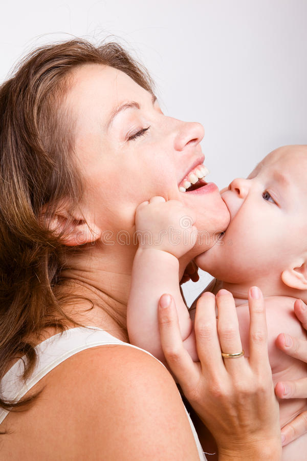 behandla som ett barn den kyssande modern royaltyfri bild