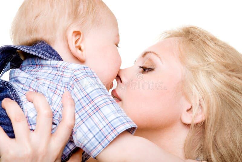 behandla som ett barn den kyssande momen arkivfoto