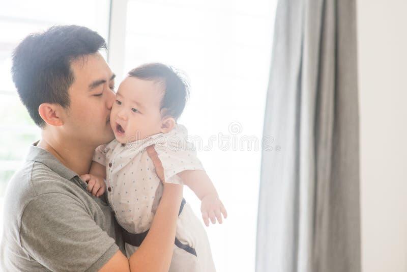 behandla som ett barn den kyssande sonen för fadern royaltyfri bild