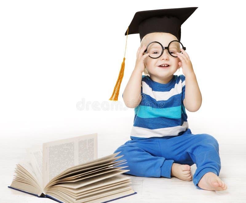 Behandla som ett barn den lästa boken, den smarta ungepojken i exponeringsglas och akademikermössahatten royaltyfri fotografi