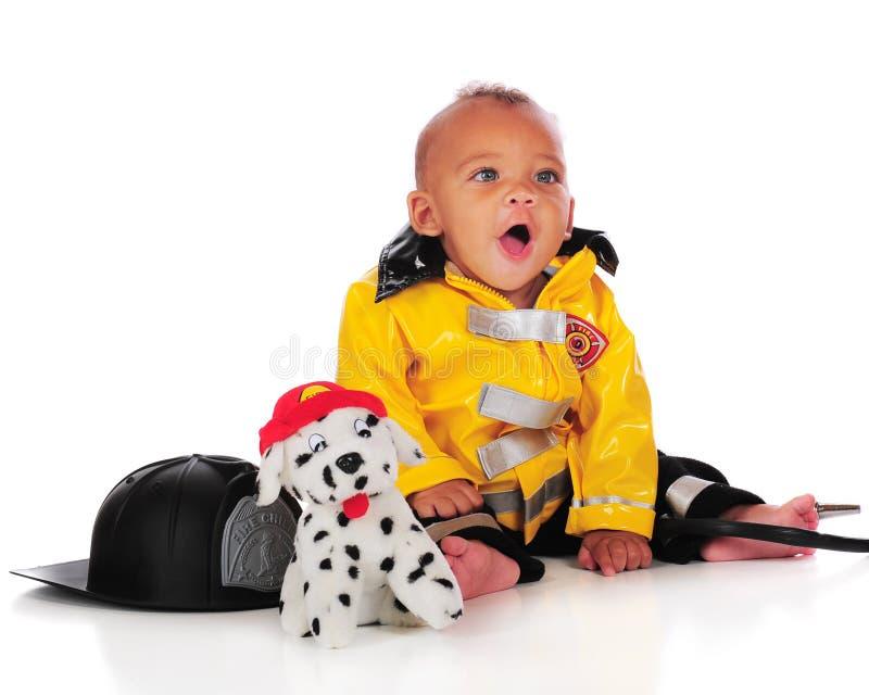 behandla som ett barn den lyckliga brandmannen arkivbild