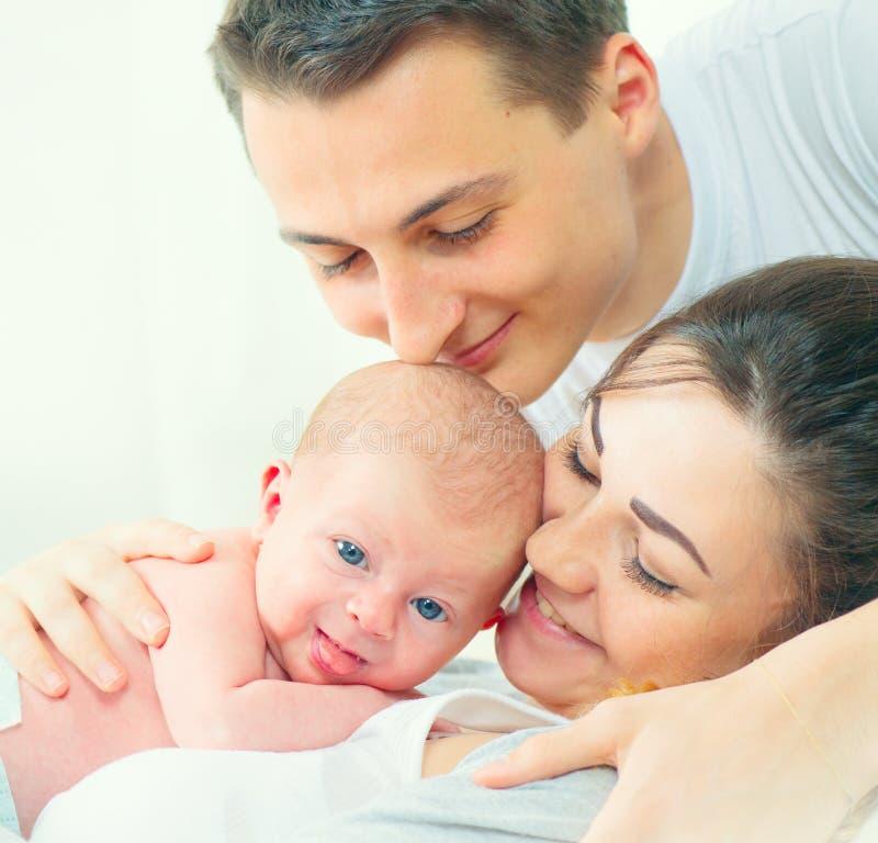 behandla som ett barn den lyckliga isolerade modern för bakgrundsfamiljfadern över le vitt barn Fadern, modern och deras nyfött b royaltyfri bild