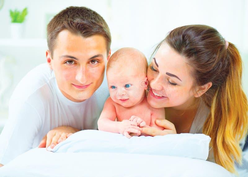 behandla som ett barn den lyckliga isolerade modern för bakgrundsfamiljfadern över le vitt barn Fadern, modern och deras nyfött b arkivbilder