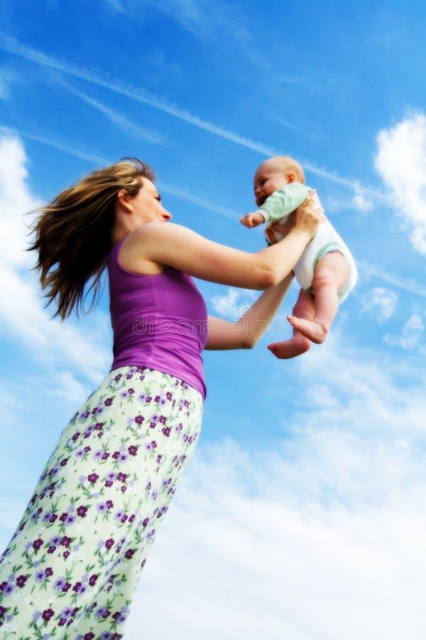 behandla som ett barn den lyckliga modern royaltyfri bild