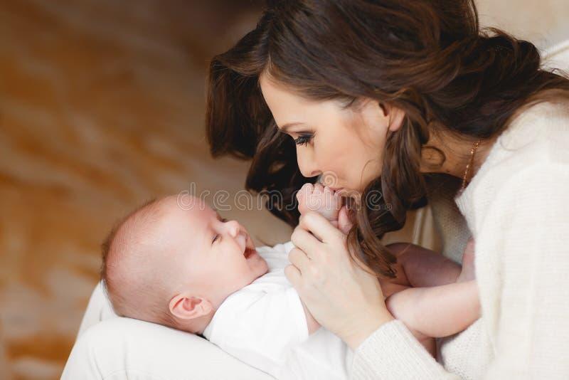 behandla som ett barn den nyfödda lyckliga modern arkivfoto