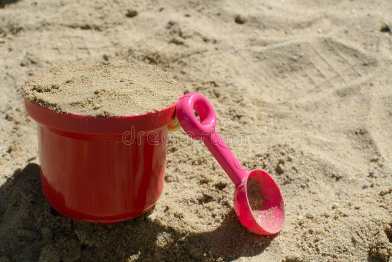 Behandla som ett barn den röda hinken och den rosa skopan i sandlådan royaltyfri fotografi