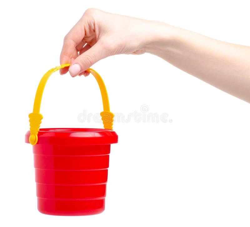 Behandla som ett barn den röda sandlådahinkleksaken i hand royaltyfri foto