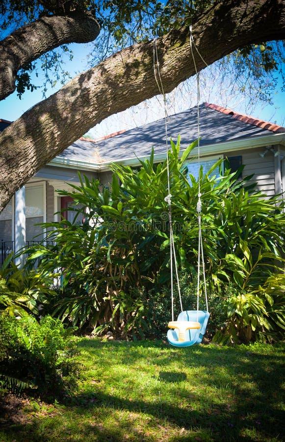 behandla som ett barn den trädgårds- swinggården arkivfoto