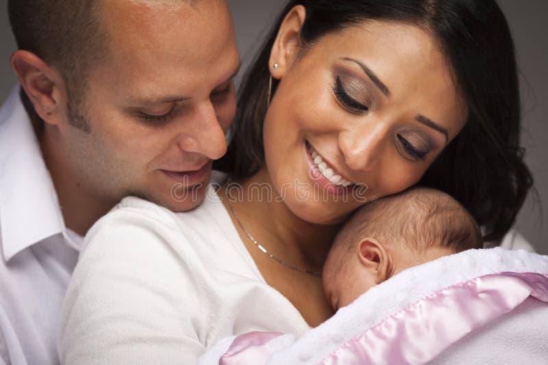 Behandla som ett barn den unga familjen för den blandade racen med nyfött fotografering för bildbyråer