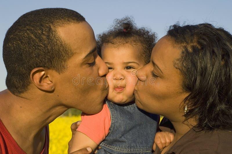 behandla som ett barn deras kyssande föräldrar arkivfoto