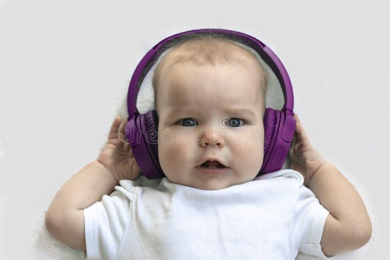 Behandla som ett barn det lyckliga barnlilla barnet le i tr?dl?s purpurf?rgad h?rlurar p? en vit bakgrund Begreppet av teknologi  arkivbild
